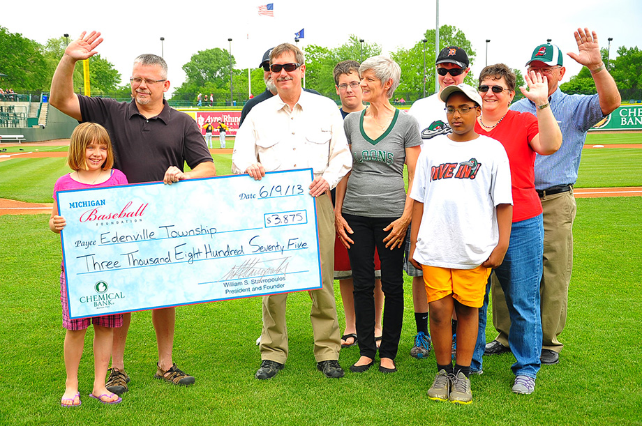 People from Michigan Baseball Foundation give check at baseball game.